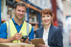 Worker and manager scanning package in warehouse Royalty Free Stock Image