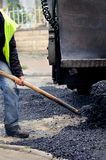 Worker manually effusing asphalt with paving machine Royalty Free Stock Images