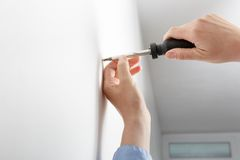 Worker manually tightening hang screw Royalty Free Stock Photo
