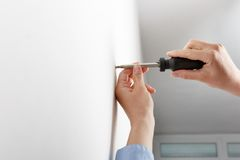 Worker manually tightening hang screw. Worker manually tightening an artwork hang screw into a drilled hole in white wall with screwdriver, renovating Royalty Free Stock Photo