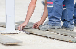 Worker marking plank for cutting Royalty Free Stock Photo