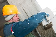 Worker mason at bricklaying work Royalty Free Stock Image