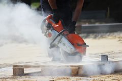 A worker mason cuts a curb with a circular saw when building a parking lot for tourist buses. Royalty Free Stock Photography