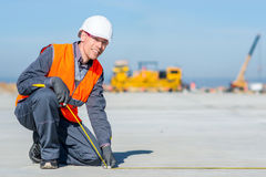 Worker measure construction. Builder measure construction runway airport new concrete Royalty Free Stock Photo