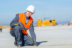 Worker measure construction. Builder measure construction runway airport new concrete Stock Images