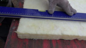 Worker measure and cut  insulation material rock wool stock video footage