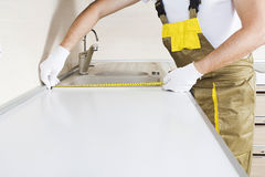 Worker measure kitchen furniture. With measuring tape Stock Photo