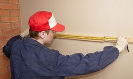 The worker measures. Wooden panel Stock Photo