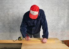 The worker measures. The distance and puts a mark Stock Photography
