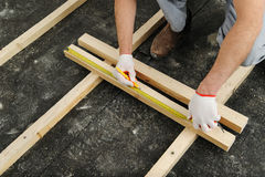Worker measures off a wooden beam. Royalty Free Stock Photo