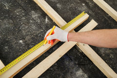 Worker measures off a wooden beam. Royalty Free Stock Photography
