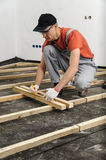 Worker measures off a wooden beam. Royalty Free Stock Images