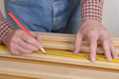Worker measures the plank Royalty Free Stock Photography