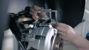 The worker measures the width of the wheel. Master measures the width of the disc caliper to the wheel. A man dressed in a blue overalls. Master checks the stock footage