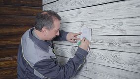The worker measures a wooden wall with a ruler. Hd stock footage