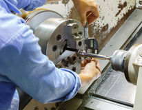 Worker measuring cnc turning part ny micro meter. On macchine Royalty Free Stock Photography