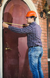 Worker measuring door with measuring tape Royalty Free Stock Images