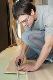Worker measuring at flooring works Royalty Free Stock Image