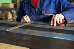 Worker measuring fresh welded steel bar. Worker measuring fresh welded stainless steel bar royalty free stock photos