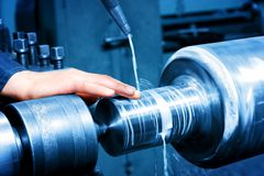 Worker measuring on industrial turning machine. Industry Royalty Free Stock Image
