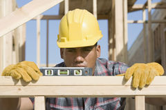 Worker Measuring Level At Construction Site. Male worker using spirit level at construction site Stock Photo