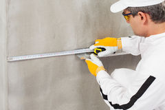 Worker measuring the level of a lath Royalty Free Stock Image
