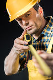 Worker measuring with meter roller. Portrait of pensive male worker measuring with meter roller Stock Images