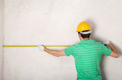 Worker measuring plaster wall Royalty Free Stock Image