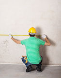 Worker measuring plaster wall Stock Image