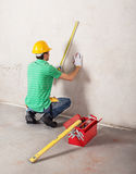Worker measuring plaster wall Stock Photography