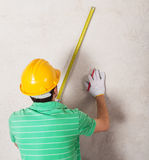 Worker measuring plaster wall Royalty Free Stock Photo