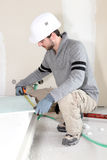 Worker measuring plasterboard. To ensure it fits Royalty Free Stock Images