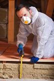Worker measuring the thickness of heat insulation. Layer estimating energy efficiency of a house Royalty Free Stock Photo
