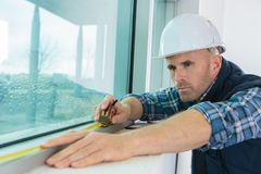 Worker measuring window at construction site Royalty Free Stock Images