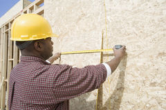 Worker Measuring Wooden Sheet At Site Stock Image