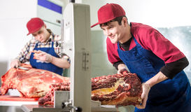 Worker at a meat factory. Cutting big piece of meat Royalty Free Stock Photos