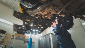Worker mechanic checks the bottom of car - automobile service Stock Image