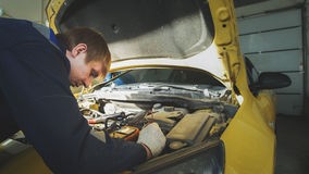 A worker mechanic checks the electrical in the hood of the yellow car- repairing in engine compartment Royalty Free Stock Images