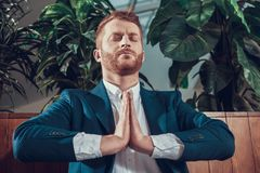 Worker meditating on bench in office. Stock Photography