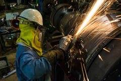 Worker metal grinding machine repair weld at steel roll.  Stock Photo