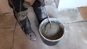 Worker mix adhesive cement for tile on bucket with tool stock video