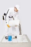 Worker mix tile adhesive bucket  of water white tiles Royalty Free Stock Image