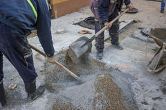 Worker is mixing the cement by hand. Close up, old fashioned way stock image