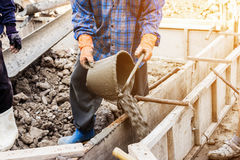 Worker mixing cement mortar plaster for construction Stock Photos