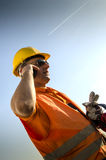 Worker with mobile phone anti phones and gloves Royalty Free Stock Photography