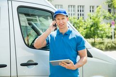 Worker With Mobile Phone And Digital Tablet Royalty Free Stock Photo