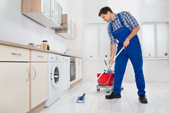 Worker Mopping Floor In Kitchen. Young Male Worker Mopping Floor In Kitchen At Home Stock Photos