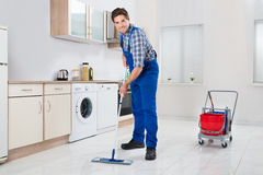 Worker Mopping Floor. Young Happy Worker In Overall Mopping Floor Royalty Free Stock Images