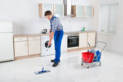 Worker Mopping Floor. Young Happy Worker In Overall Mopping Floor Stock Photography