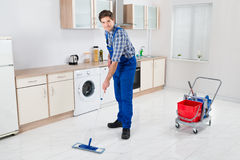 Worker Mopping Floor. Young Happy Worker In Overall Mopping Floor Stock Photos